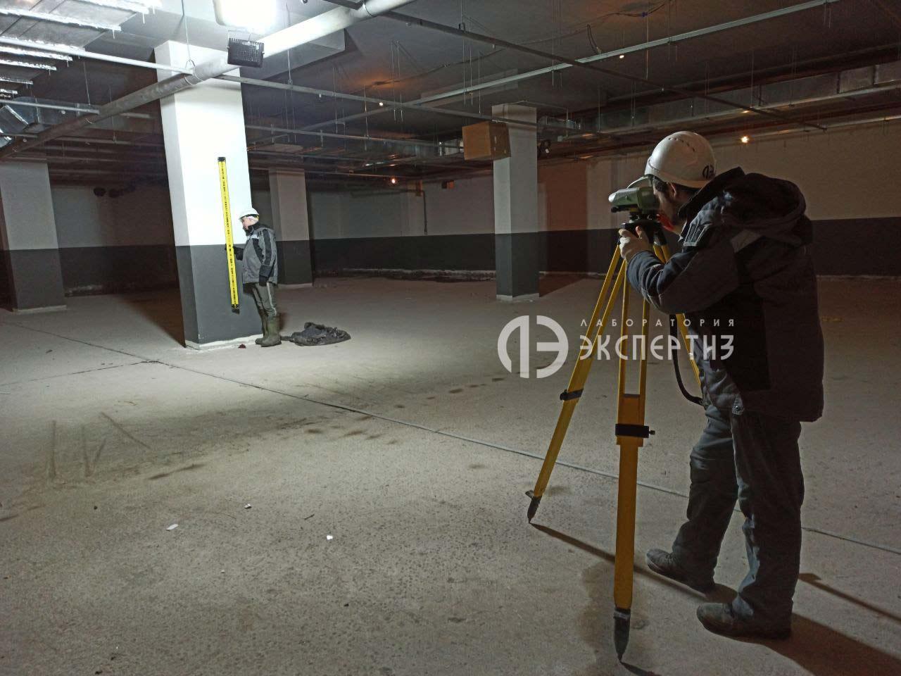 Специалисты с нивелиром на подземной парковке