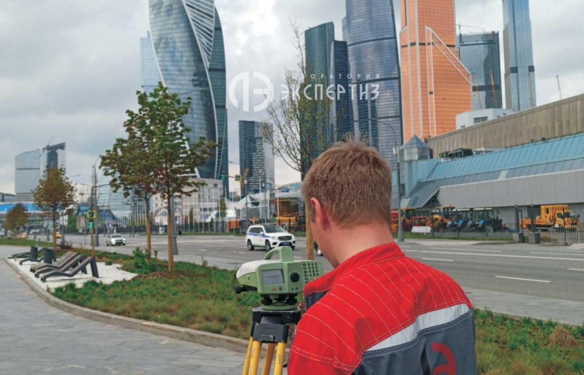Специалист с нивелиром делает геотехнический мониторинг Москва-Сити