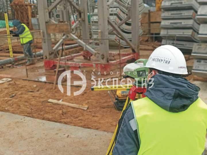 Специалисты с инварной рейкой и нивелиром на строительстве станции славянский мир