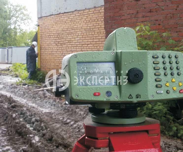 Нивелир и специалист с инварной рейкой при геотехническом мониторинге
