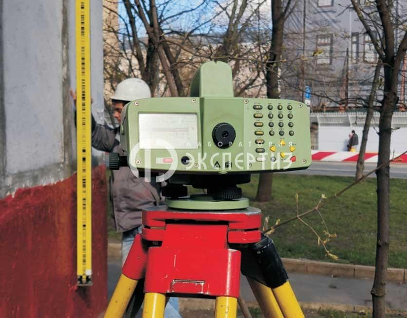 Геотехнический мониторинг нивелир и инварная рейка у геодезиста.