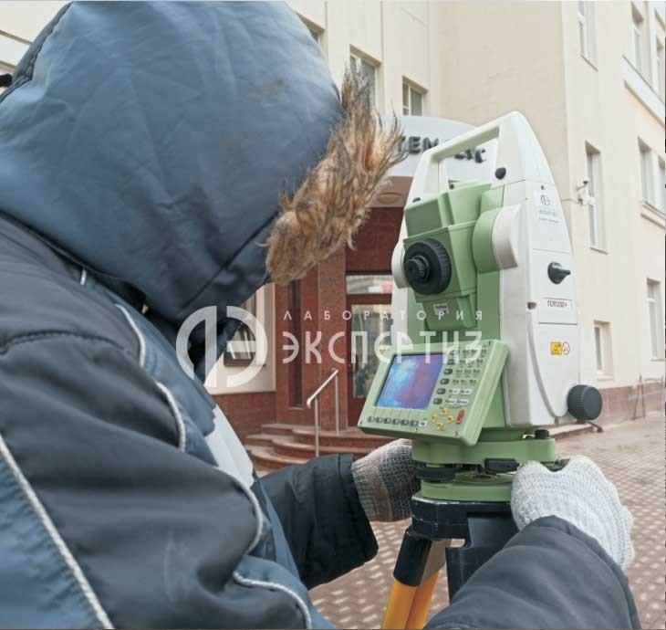 Геодезист делает Геотехнический мониторинг с помощью нивелира